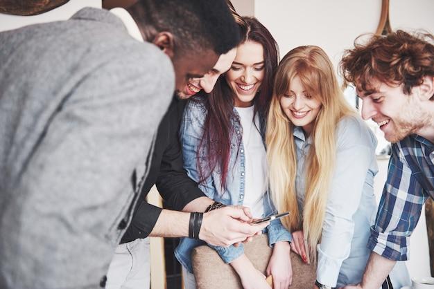 Портрет веселых молодых друзей, глядя на смартфон, сидя в кафе