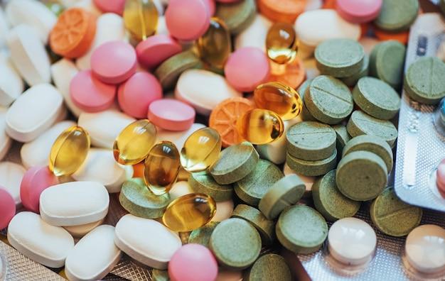 医療のカラフルな錠剤、カプセルまたは明るい背景に治療や健康管理のためのサプリメント
