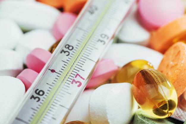 温度計と異なる色の丸薬。医療の健康や薬の概念