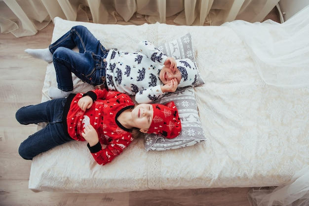 ベッドで遊ぶ柔らかく暖かいパジャマの子供