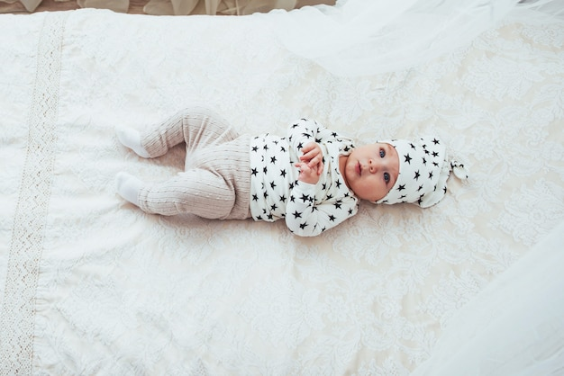白いスーツと黒い星に身を包んだ新生児はスタジオの白い柔らかいベッド