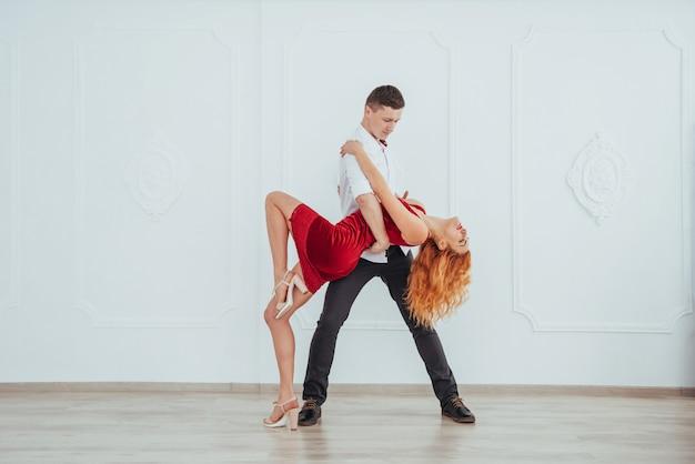 Молодая красивая женщина в красном платье и танцы человека изолированные на белой предпосылке.