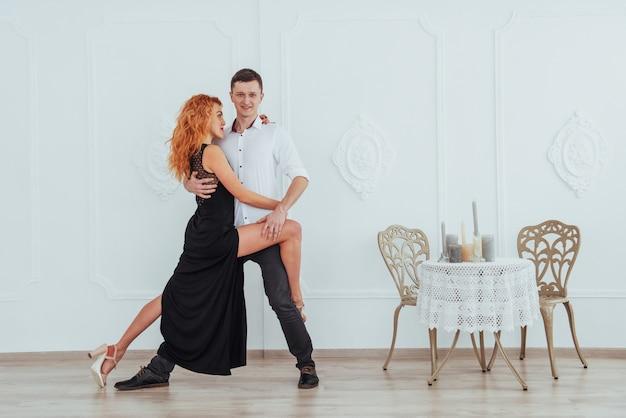 Молодая красивая женщина в черном платье и мужчина в белой рубашке танцы.