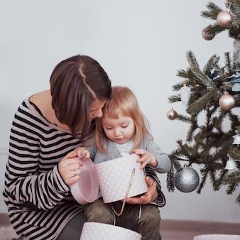 Счастливая семья, мама и малыш украшают елку