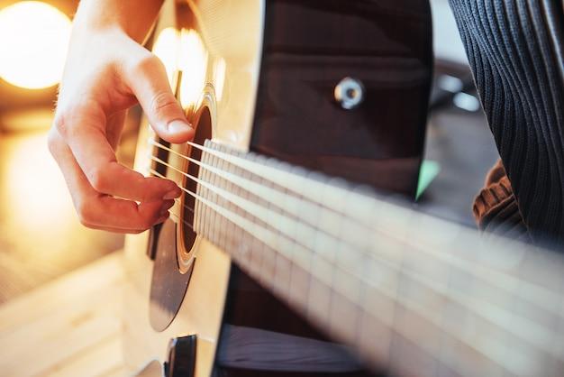 ギタリストは木製の背景でギターを弾く