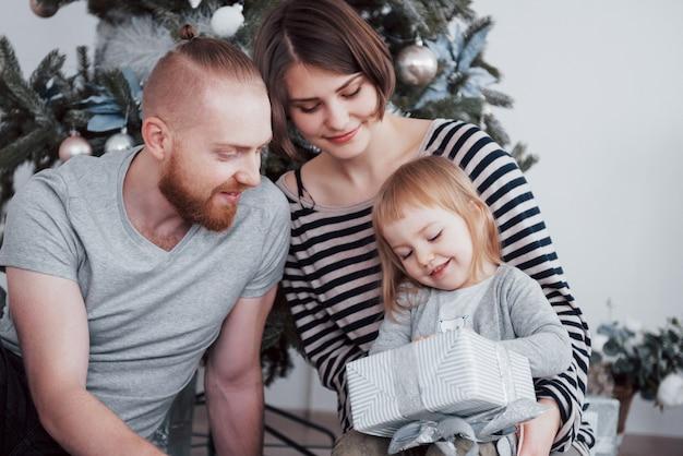 モミの木の近くで一緒に贈り物を開く朝のクリスマスに幸せな家族。家族の幸せと幸福の概念
