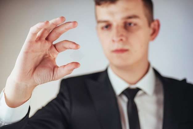 スーツの青年実業家は彼の手を示しています