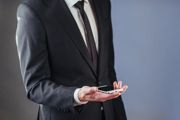 彼の手で携帯電話を持ったビジネスマン。