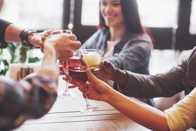 ウイスキーやワインのグラスを持つ人々の手、祝うと乾杯