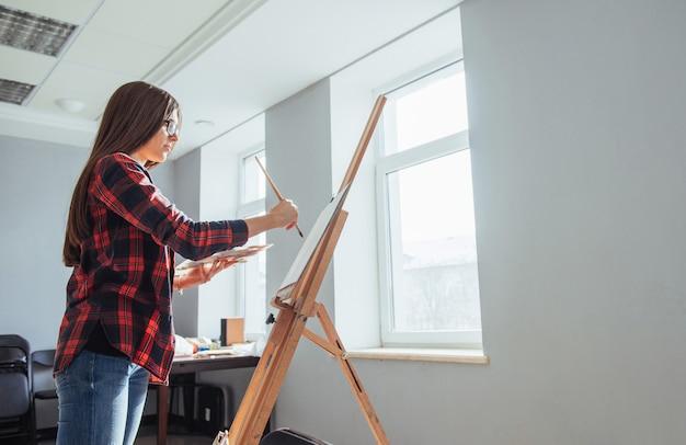 Художник молодой женщины рисует картину