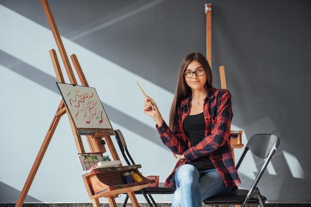 Темноволосый художник держит кисть в руке и рисует картину на холсте.