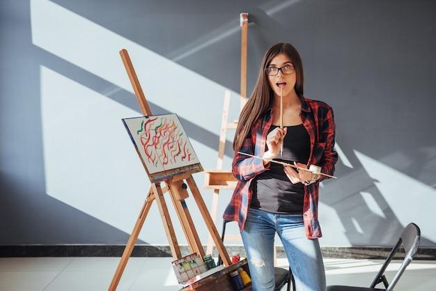 創造的な物思いにふける画家少女は、ワークショップでキャンバスにカラフルな絵をオイルの色でペイントします。