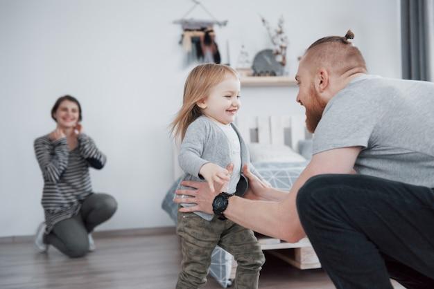 幸せな家族は家で楽しんでいます。母、父、ぬいぐるみを持つ小さな娘が一緒にいることを楽しんでいます。
