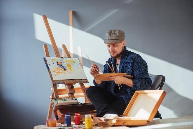 彼の傑作を仕上げるアーティストの男によって設計された手にブラシを保持しています。