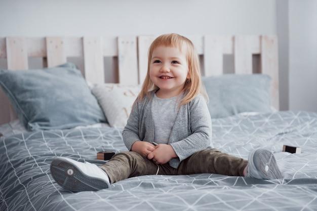 Счастливая маленькая девочка с подушкой в постели у себя дома