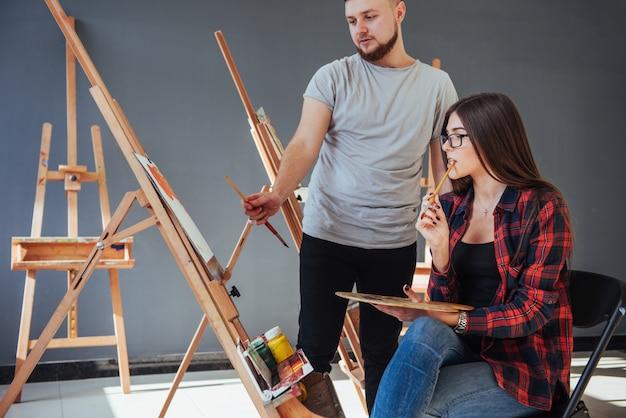 Творческие художники рисуют красочную картину на холсте масляными красками