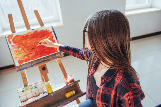 かなりきれいな女の子のアーティストは、イーゼルにキャンバスの絵を描きます。
