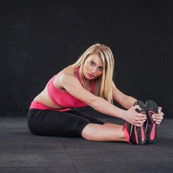 Практика йоги. девушка в фитнес зале выполняет растяжку.