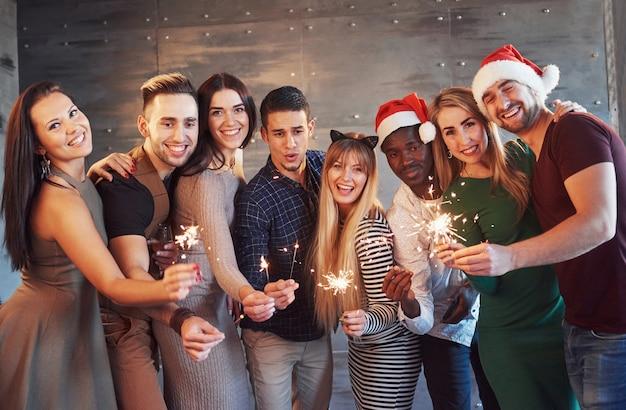 Вечеринка с друзьями. группа веселых молодых людей, несущих бенгальские огни и флейты шампанского