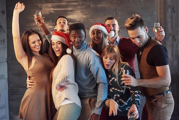 友達とパーティー。彼らはクリスマスが大好きです。新年パーティーで踊って幸せそうに見える花火とシャンパンフルートを運ぶ陽気な若者のグループ。一体性のライフスタイルに関する概念