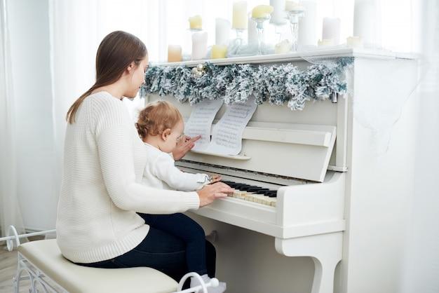 白いピアノを弾く母と娘を後ろから見る