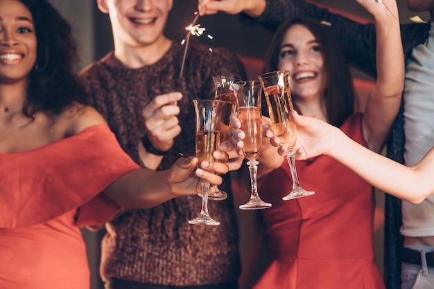 シャンパンは不可欠な部分です。多民族の友人が新年を祝うとドリンクを飲みながらベンガルライトとグラスを保持