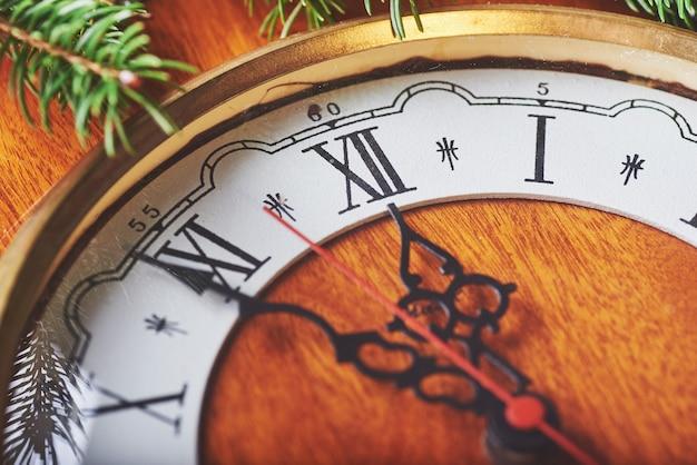 真夜中に幸せな新年、古い木製時計とモミの枝
