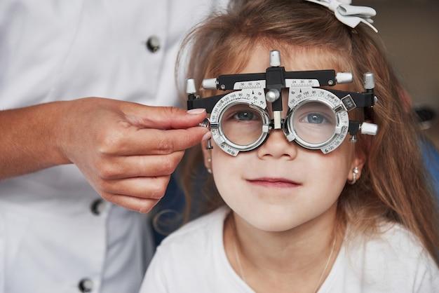 小さな女の子の視力をチェックし、フォロプターを調整する医師