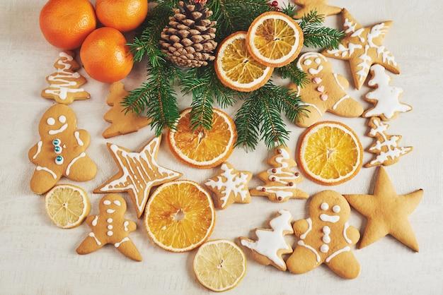 クリスマスジンジャーブレッドクッキーと乾燥オレンジと白いテーブルの上のスパイス。クリスマスツリー、コーン、クリスマスデコレーションの椅子
