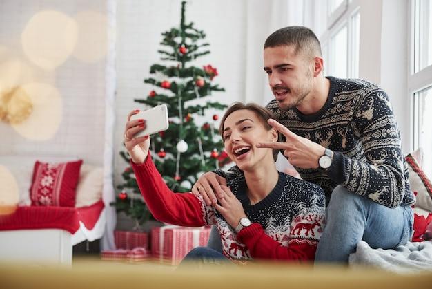 Принимая селфи. парень показывает жест двумя пальцами. счастливые молодые люди сидят на подоконнике в комнате с елочными украшениями