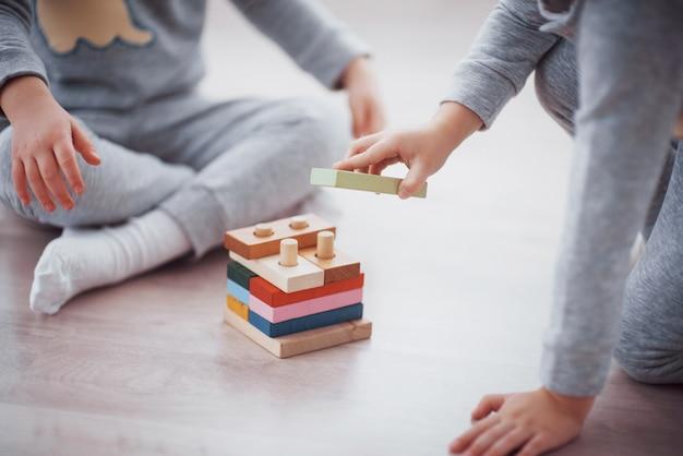 Дети играют с игрушечным конструктором на полу детской комнаты.