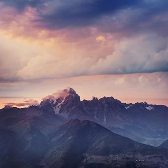 霧の中で雪に覆われた山々。コルルディ湖の秋