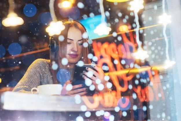 Молодая красивая женщина, сидя в кафе, пить кофе. модель слушает музыку.