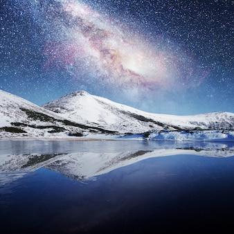 雪をかぶった山々の間の湖。幻想的な星空
