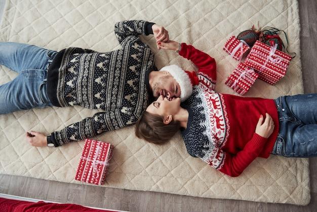 クリスマスの服のカップルのトップビューは床に横たわってギフト