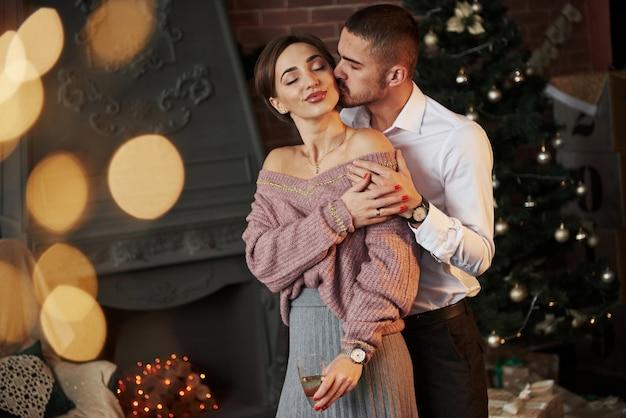 男は彼の最愛の少女にキスします。素敵なカップルは、クリスマスツリーの前でシャンパンと新年を祝うガラスを保持しています。