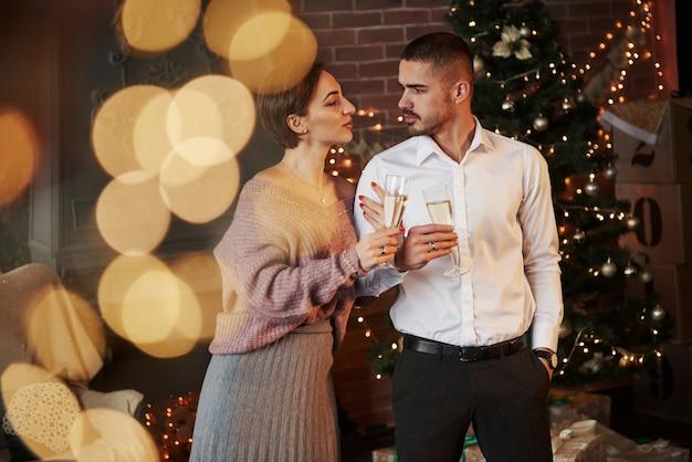 女性は夫にしがみついています。クリスマスツリーの前で新年を祝う素敵なカップル