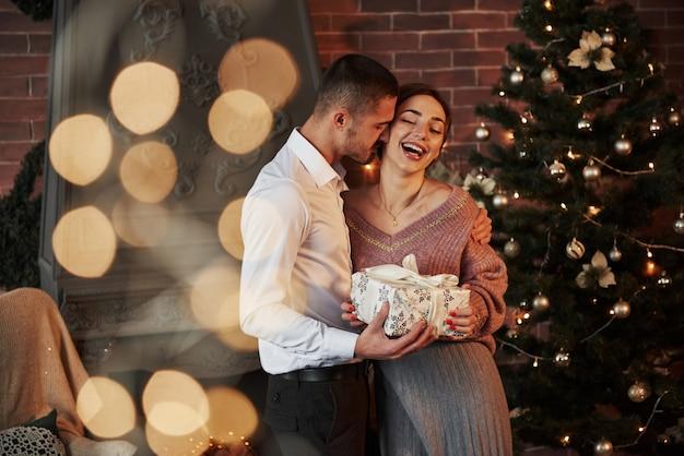 新年の幸せ。女性へのクリスマスプレゼント。古典的なスーツを着た紳士が妻にプレゼントを贈る