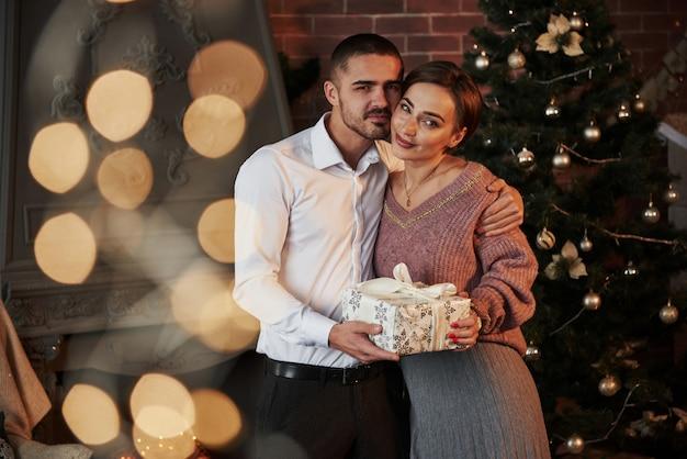 カメラを見ています。女性へのクリスマスプレゼント。古典的なスーツを着た紳士が妻にプレゼントを贈る