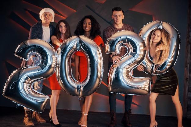Группа красивых молодых людей празднуют новый год.