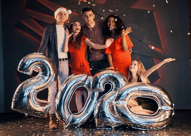 Группа веселых молодых красивых многонациональных людей, бросающих конфетти на вечеринке. с новым годом.