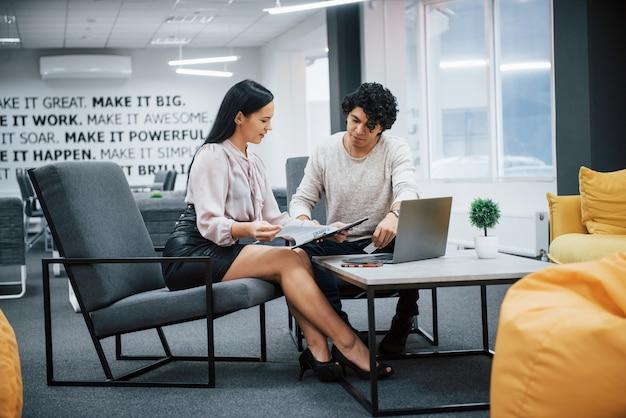 巻き毛の男とブルネットの少女は、近代的なオフィスでの契約の詳細について説明します