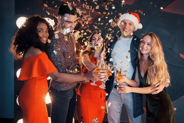 ポーズをとって雪だるまとシャンパンを楽しんでいる友人のグループ。新年のお祝い。