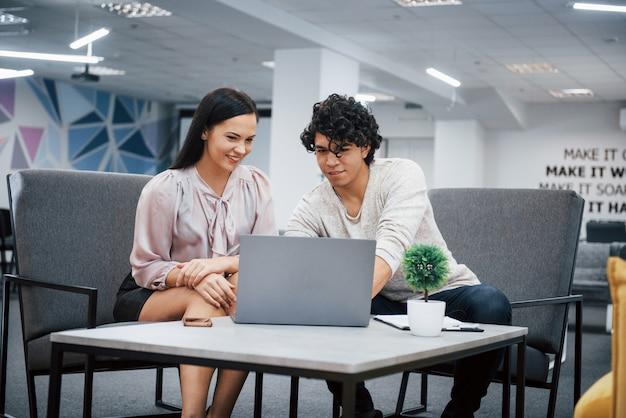 ラップトップを使用して作業します。巻き毛の男とブルネットの少女は、近代的なオフィスでの契約の詳細について説明します