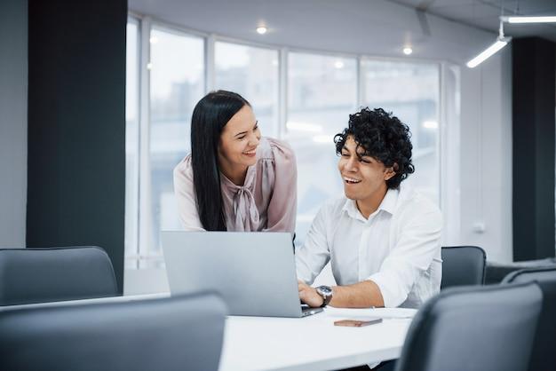 Веселые коллеги в современном офисе, улыбаясь при выполнении своей работы с помощью ноутбука