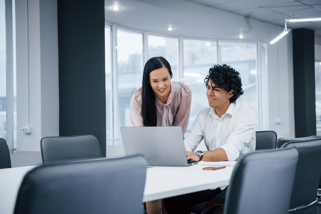 コンピューターを一緒に見ています。ラップトップを使用して仕事をしているときに笑みを浮かべて近代的なオフィスで陽気な同僚
