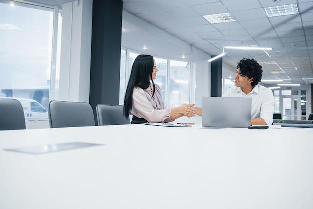 Удачная сделка между двумя людьми, которые сидят возле стола и ноутбука на нем в белом кабинете