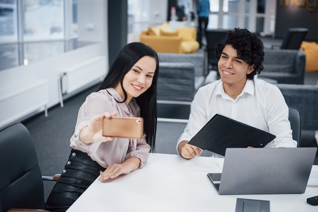 Селфи двух улыбающихся офисных работников в официальной одежде, сидящих рядом с серебряным ноутбуком на столе