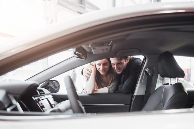 Принятие решения. красивая влюбленная пара выбирает новый автомобиль