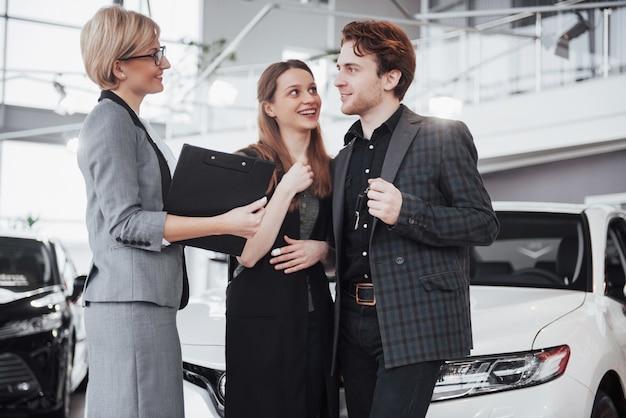 Теперь ее мечта сбывается. продавец автомобилей вручает ключи от нового автомобиля молодым привлекательным владельцам